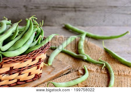 Fresh green beans in a brown wicker basket on a wooden board and a burlap textile. Rustic wooden background