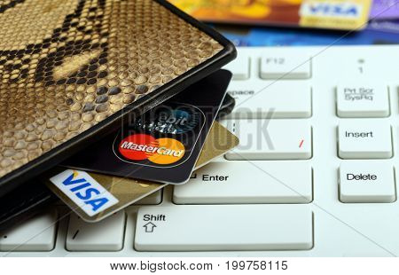 Moscow, Russia - August 05, 2017: Visa and mastercard credit cards in wallet over white keyboard