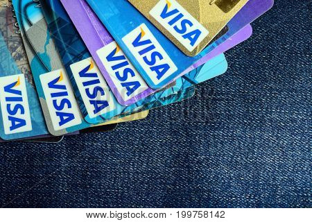 Moscow, Russia - August 05, 2017: Visa credit cards over blue jeans