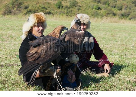 ALMATY, KAZAKHSTAN - SEPTEMBER 18, 2011: Unidentified men hold golden eagles (Aquila chrysaetos) Almaty, Kazakhstan.