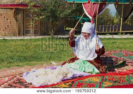 ALMATY, KAZAKHSTAN - SEPTEMBER 18, 2011: Unidentified women wearing traditional dress produces felt in Almaty, Kazakhstan.