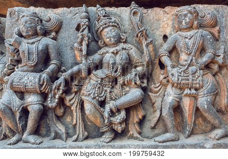 Example of ancient Indian architecture and traditional style relief with drummer musicians and dancing Hindu goddess inside the 12th century Hoysaleshwara temple in Halebidu, India.