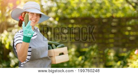 Smiling girl in hat holds cucumber in hand and box under arm