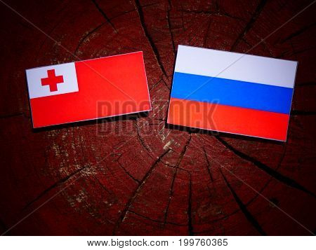 Tonga Flag With Russian Flag On A Tree Stump Isolated