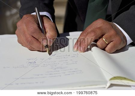 A witness signing the legal documents in a wedding