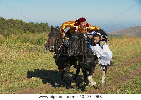 CIRCA ALMATY, KAZAKHSTAN - SEPTEMBER 18, 2011: Unidentified people wearing national dresses ride on horseback at countryside Almaty, Kazakhstan.