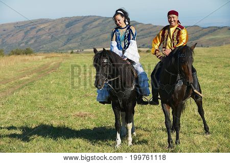 CIRCA ALMATY, KAZAKHSTAN - SEPTEMBER 18, 2011: Unidentified people wearing traditional national dresses ride on horseback at countryside Almaty, Kazakhstan.