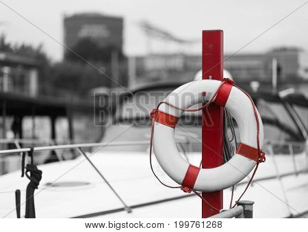 red lifebelt in front of a ship in a marina
