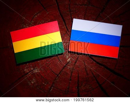 Bolivian Flag With Russian Flag On A Tree Stump Isolated