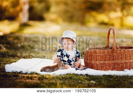Little boy playing with rabbits in the park, summer and autumn landscape. Concept first childhood acquaintance, friends with animals.