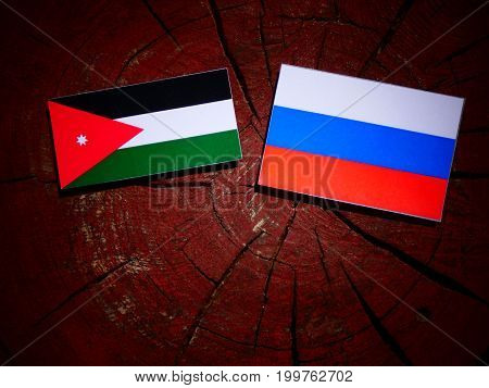 Jordanian Flag With Russian Flag On A Tree Stump Isolated
