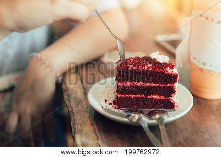 eating Red Velvet strawberry cheese cake decorated with cream.