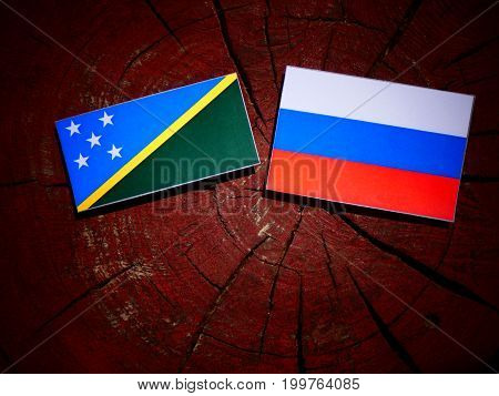 Solomon Islands Flag With Russian Flag On A Tree Stump Isolated