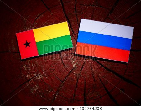 Guinea Bissau Flag With Russian Flag On A Tree Stump Isolated