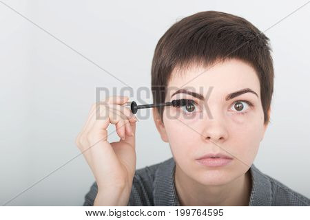 Beauty make-up. Portrait of young girl with fake eyelashes applying black mascara on lashes, holding brush in hand. Sexy female with soft skin and perfect makeup. Cosmetics.