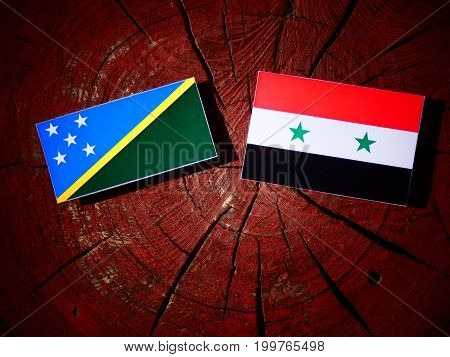 Solomon Islands Flag With Syrian Flag On A Tree Stump Isolated