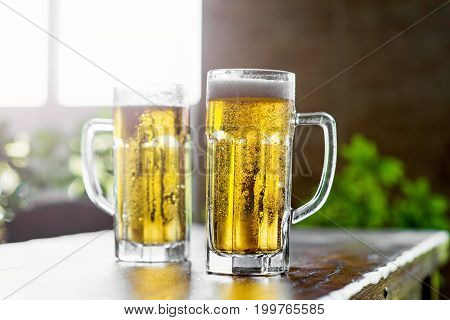 Two glasses of cold beer on a wooden bar table. Closeup.