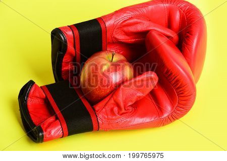 Sport equipment and fruit isolated on yellow background. Professional box fight and dieting concept. Boxing gloves in red color. Pair of leather boxing sportswear with juicy red apple