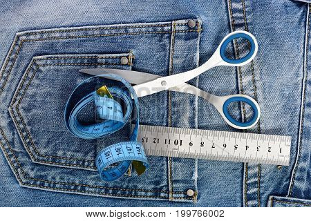Tailors tools with denim textile. Tailoring and design concept. Metal scissors ruler and blue measure tape in denim pants pockets. Things for making clothes in back pockets of jeans top view.