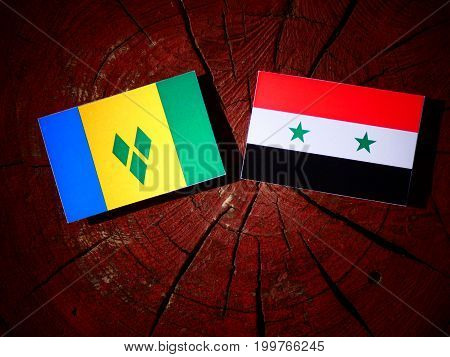 Saint Vincent And The Grenadines Flag With Syrian Flag On A Tree Stump Isolated