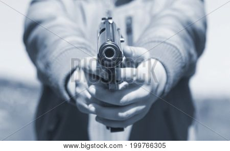 Gun aimed at you. Gun in hands front view. Kid shooting