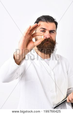 Physician With Concentrated Face Holds Capsule