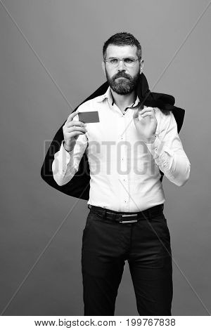 Man With Beard In White Shirt Holds Blue Business Card