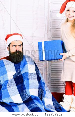 cute smiling blonde girl in beige dress gives big gift to handsome bearded man with long beard in christmas red hat in blue checkered plaid on white studio background