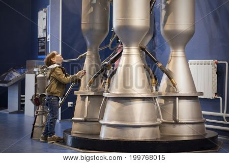 Boy studies rocket engine in museum. Boy dreams to become engineer