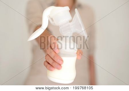 Mother holds breast pump in her hand blurred background