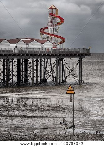 pier and helter skelter in herne bay kent in cloudy dark summer rain with beach and sea