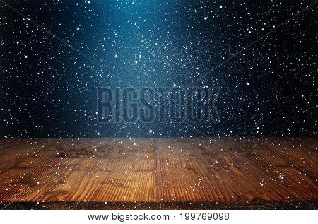 Winter background with snowflakes and old wooden table in darkness with light spot for a christmas decoration