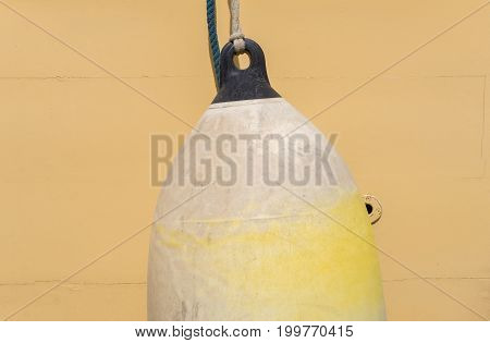 Close-up of a hanging Buoy. View of a yello Buoy on a Saling Ship. Ship supplies. Natural Background.