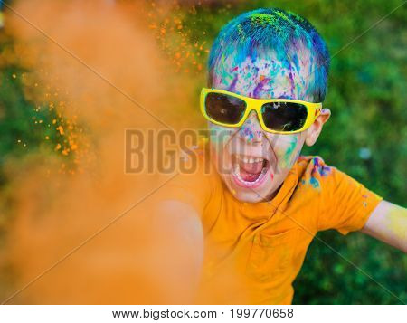 The boy in glasses throws orange paint holi