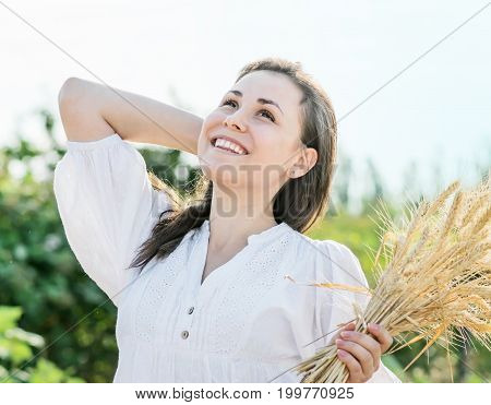 Portrait of a Beautiful laughing sexy female with long hair holding wheat ears outdoors ay summer day