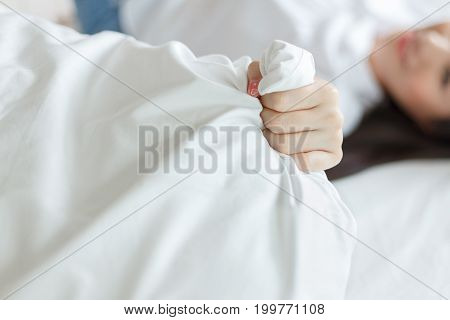 beautiful young woman hand clutching pillow on bed
