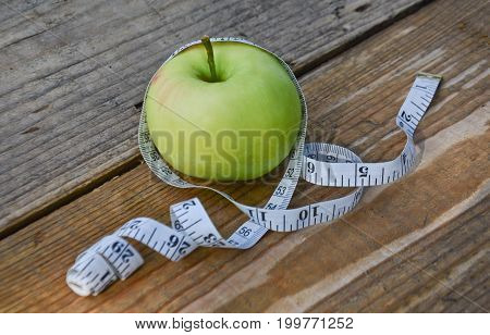 Green Apple wrapped in a meter on a wooden table