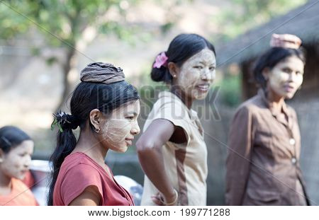 MYITKYINA, MYANMAR - JANUARY 4, 2012: Burmese girls with thanaka paste on their faces going to local market. Thanaka is a yellow cosmetic paste made from ground bark.