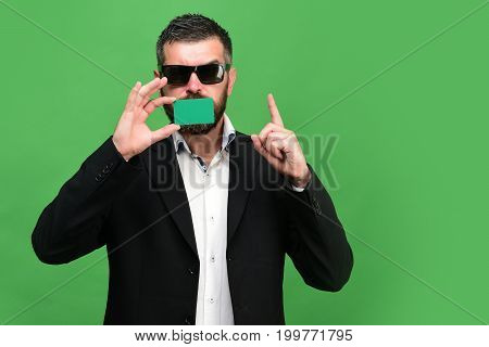 Guy With Thoughtful Face And Sunglasses Isolated On Green Background