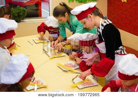 Alchevsk, Ukraine - July 30, 2017: School Cooks For Children. Learn To Cook Pasta With Sausages