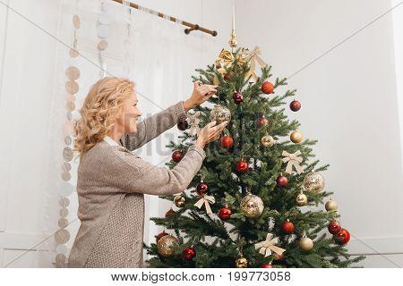view of beautiful mature woman decorating christmas tree