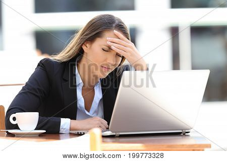 Tired businesswoman suffering head ache sitting in a coffee shop