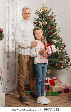 Grandfather And Granddaughter With Christmas Gift