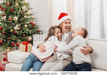 Woman And Kids In Christmas Decorated Room