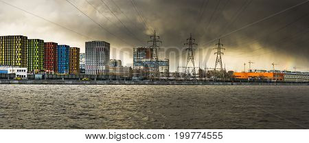Panorama of the embankment of the river with residential buildings power lines and industrial facilities against the backdrop of a stormy sky