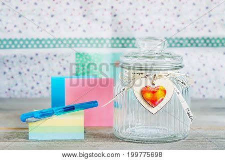 Glass jar with handmade wooden hearts decorations and ribbon near a stack of colored papers and a blue pen.