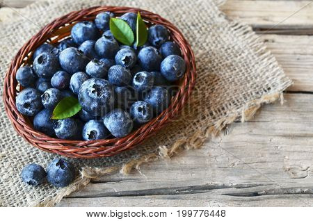 Freshly picked blueberries in a basket on burlap cloth background.Fresh blueberries with green leaves on rustic table.Blueberry.Bilberry.Healthy eating,diet and nutrition concept.Selective focus.
