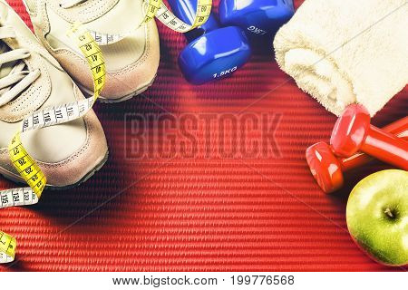 Fitness frame with dumbbells sneakers and green apple . Healthy lifestyle concept with copy space