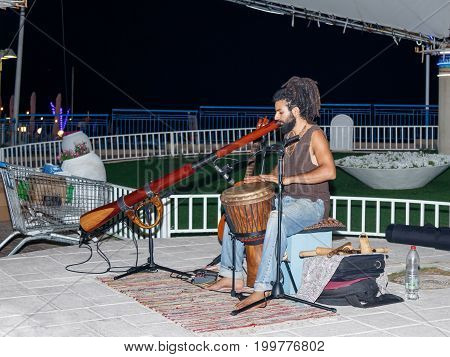 Nahariya Israel August 14 2017 : A young guy plays a darbuka and a big pipe in the evening on the waterfront in the city of Nahariya in Israel