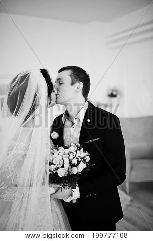 Beautiful Wedding Couple Kissing And Looking Into Each Other's Eyes In The Studio. Black And White P